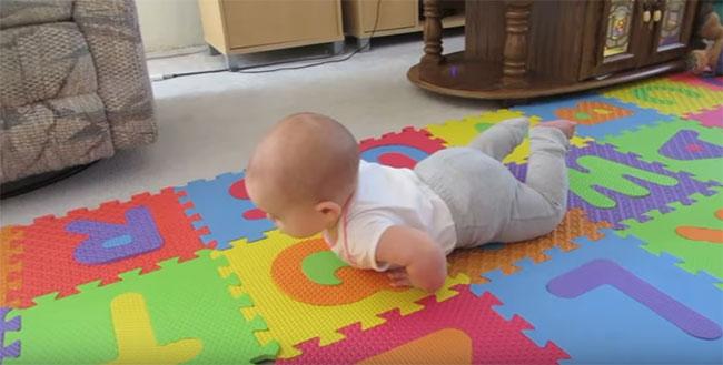 Ребенок на животе на цветном коврике