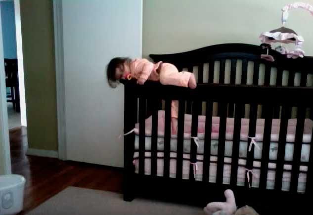 Ребенок перелазит через борты детской кроватки