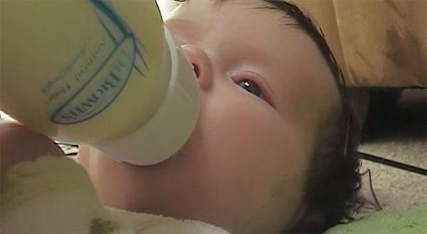 Малыш пьет молоко из бутылочки