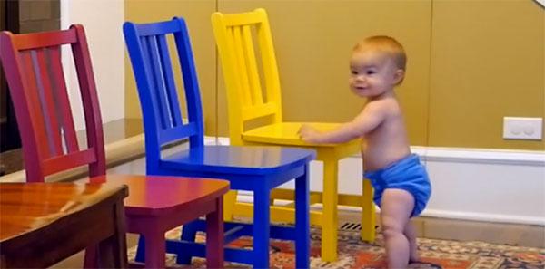 Ребенок держится за стул и идет