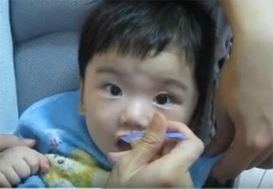 Малыша кормят овсянкой с ложечки