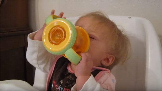 Ребенок пьет сок с бутылочки