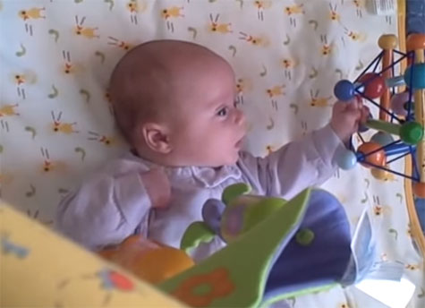 Двухмесячный ребенок следит за игрушкой
