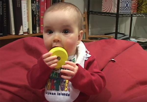 Малыш тянет в рот погремушку