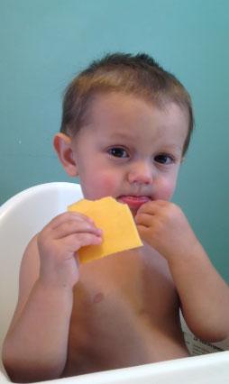 Мальчик ест сыр
