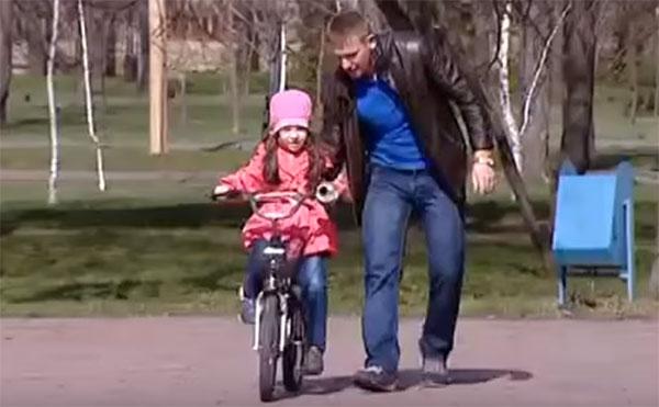 Папа учит ребенка кататься на двухколесном велосипеде