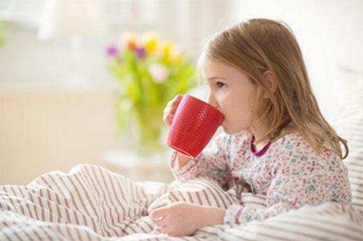 Девочка пьёт из чашки, находясь в постели