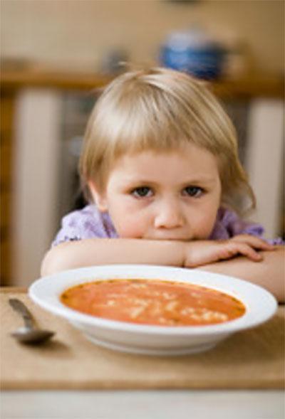 Девочка сидит перед тарелкой и не ест