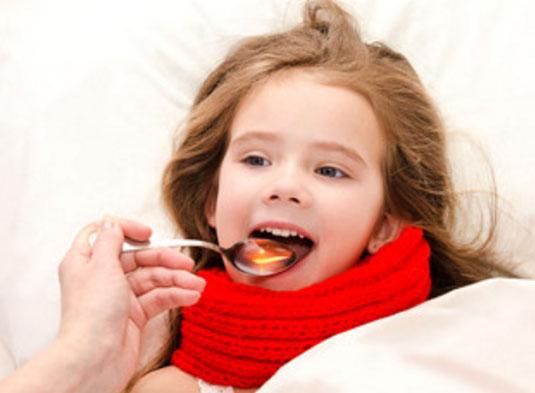 Девочке, которая лежит в постели дают сироп от температуры
