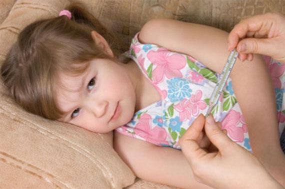 Девочка лежит на диване, мама достала градусник