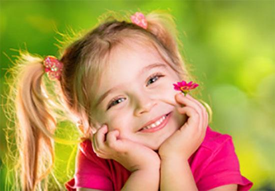 Девочка с хвостиками, держит цветочек и улыбается
