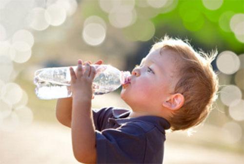 Мальчик пьет воду с бутылки