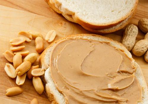 Хлеб, намазанный арахисовым маслом, рядом почищенный арахис