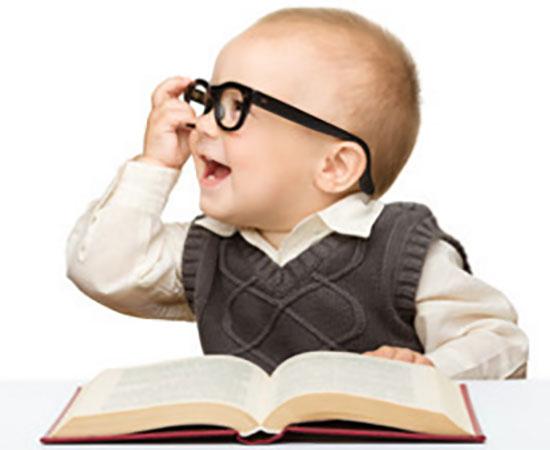 Маленький ребенок в очках сидит перед открытой книгой