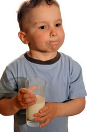 Недовольный мальчик со стаканом молока