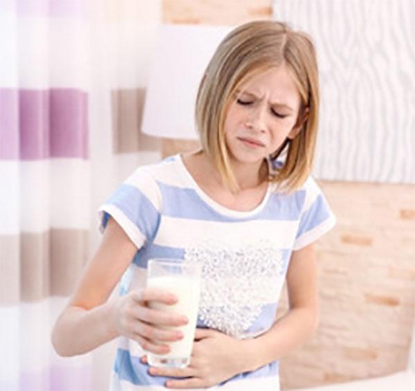 Девочка со стаканом молока держится за живот и корчится от неприятных ощущений