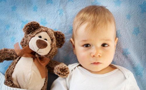 Ребенок лежит в постели, рядом с плюшевым медведем