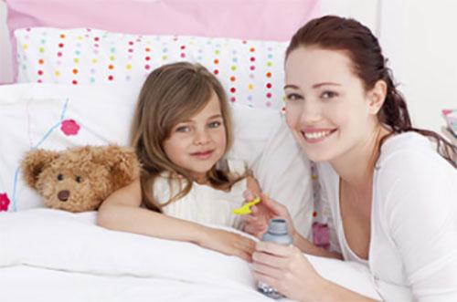 Мама дает сироп дочери, которая лежит в постели
