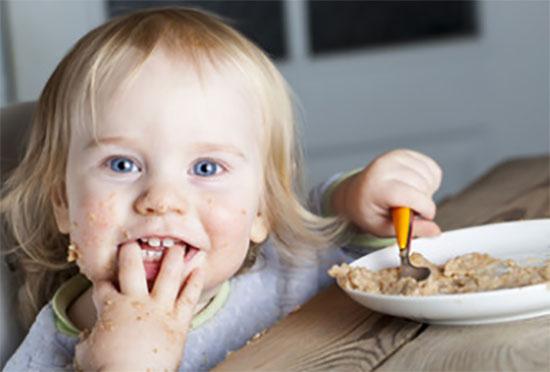 Замурзанный ребенок ест кашу