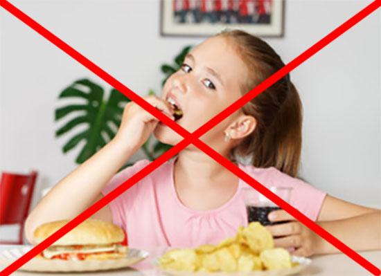 Перед девочкой чипсы, чисбургер, в руках газировка. Изображение перечеркнуто