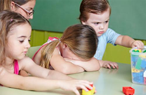 Девочка спрятала лицо, плачет. Рядом с ней серьезный мальчик, который по-видимому ее обидел и другие дети
