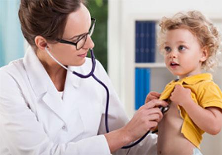 Врач фонендоскопом прослушивает ребенку грудь
