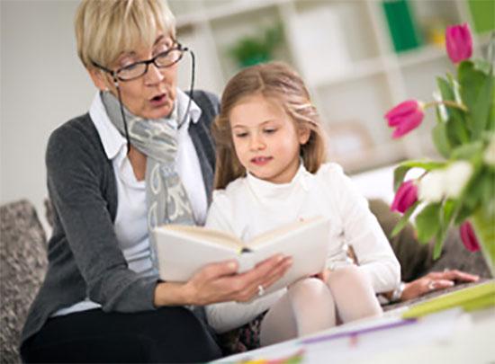 Бабушка читает внучке книгу