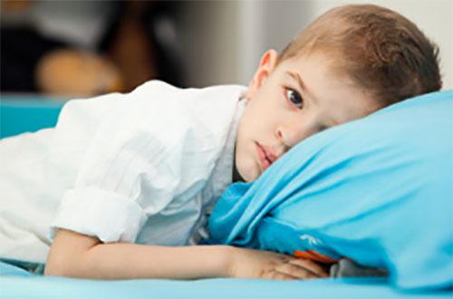 На подушке лежит грустный ребенок