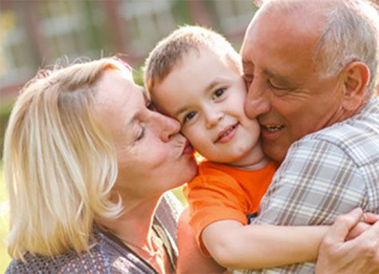 Ребенка с двух сторон обнимают бабушка и дедушка