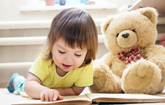 Маленькая девочка читает книгу лежа на полу, рядом сидит плюшевый медведь