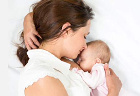 Мама лежит с грудничком, ребенок сосет грудь