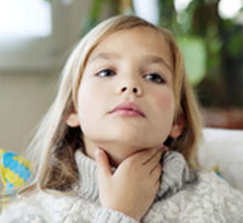 Девочка держится за больное горло