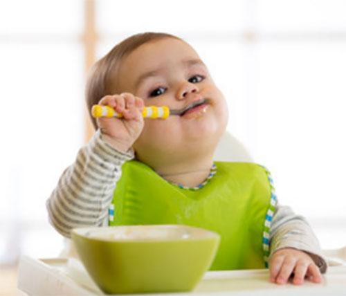 Ребенок в слюнявчике самостоятельно кушает