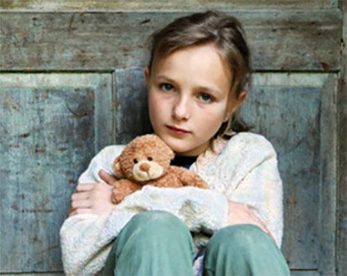 Сидит грустная девочка, в руках маленький плюшевый мишка