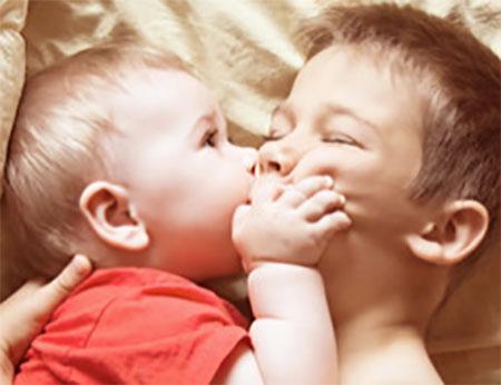 Маленький мальчик щипает более взрослого ребенка за щеку