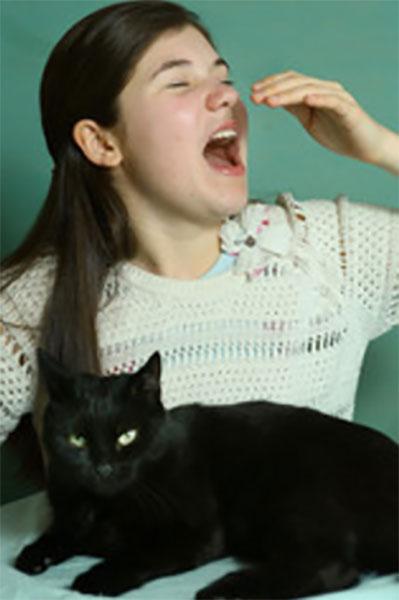 Девочка чихает, перед ней сидит кот