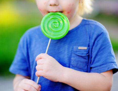 Ребенок с сыпью на щеках ест большую конфету на палочке