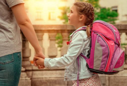 Родитель ведет девочку за руку, у ребенка на спине рюкзак