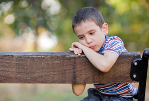 Одинокий, грустный мальчик сидит на скамейке