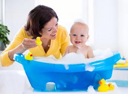 Маленький ребенок принимает ванну, рядом сидит мама