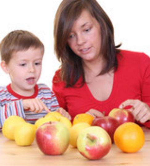 Мальчик сидит с мамой за столом и пересчитывает яблоки