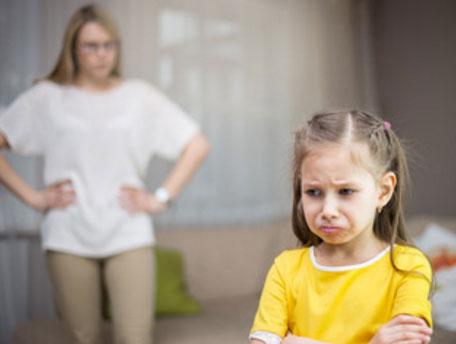 Мама за что-то наругала дочь, она стоит обиженная