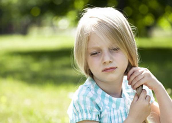 Грустная девочка на фоне солнечных лучей