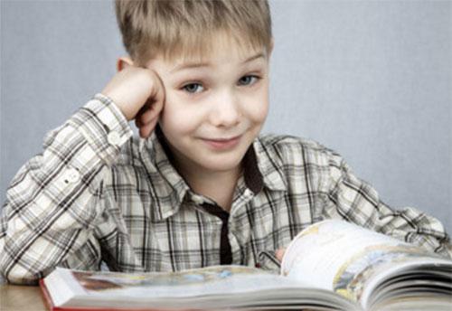 Мальчик улыбается, перед ним открытая книга
