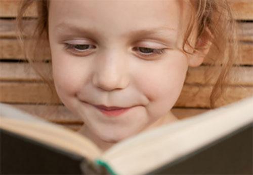 Улыбающаяся девочка читает книгу
