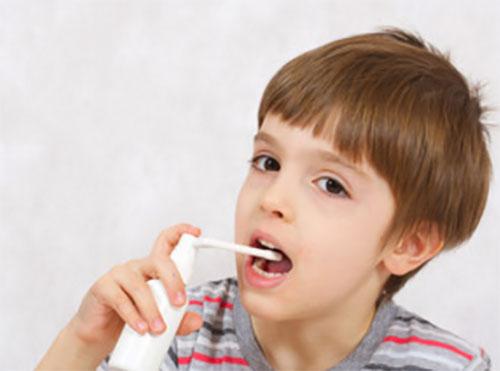 Мальчик брызгает себе горло антисептическим спреем