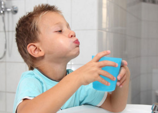 Мальчик полощет рот