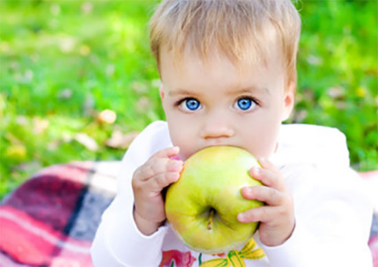 Ребенок кусает зеленое яблоко