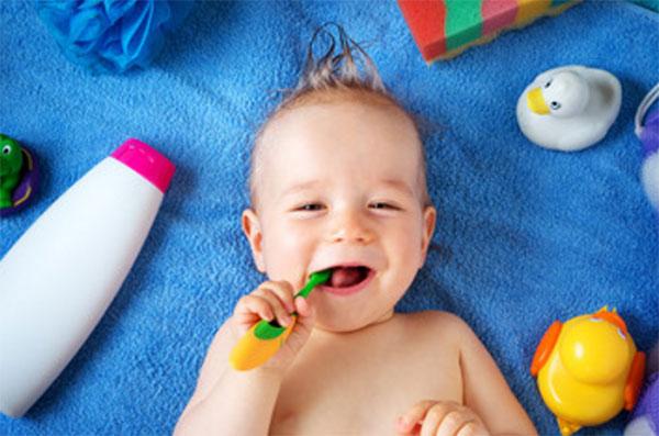 Лежит ребенок, во рту держит зубную щетку. Вокруг предметы для купания