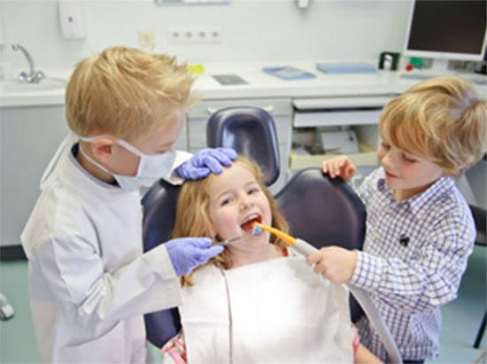 Мальчик переоделся в доктора осматривает девочку на стоматологическом кресле. Ему помогает еще один малыш